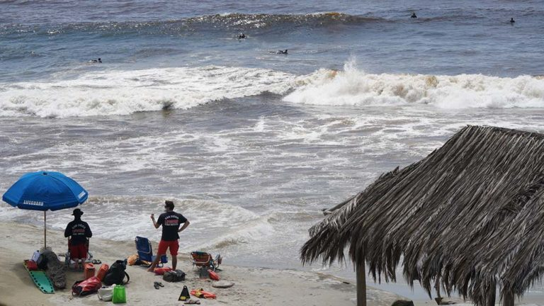 Lifeguards set up a post at Windansea as surfers flock to the waves.