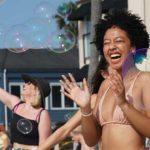 Women enjoy a barrage of bubbles made by Alan James at the Ocean Beach Pier.