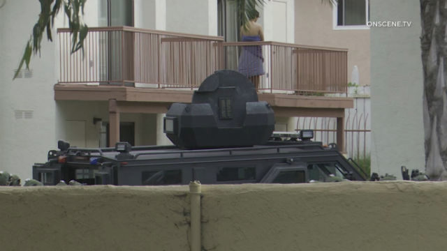 Suspect stands on balcony above SWAT team vehicle