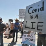 A protester with a sign joins hundreds of people in Pacific Beach calling for an end to stay-at-home orders.
