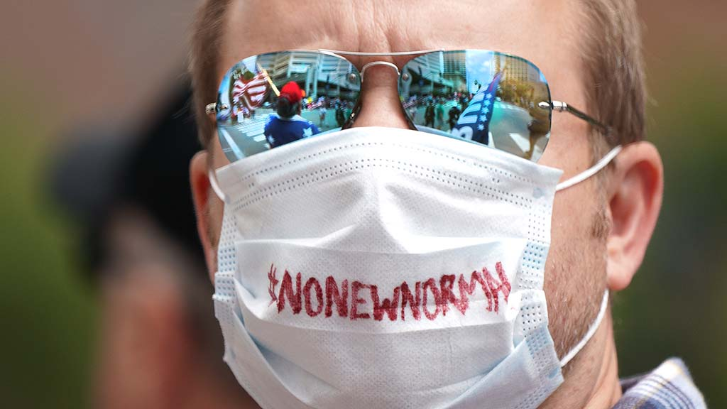 A protestor expressed a sentiment about loosening shutdown restrictions on his surgical mask.