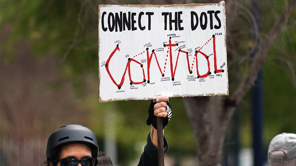 A protester's sign show events that she feels are connected to the coronavirus pandemic.