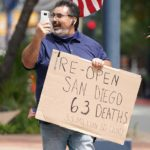 A protestor questions the number of deaths versus the county's population.