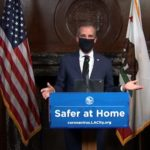Eric Garcetti demonstrates a face mask