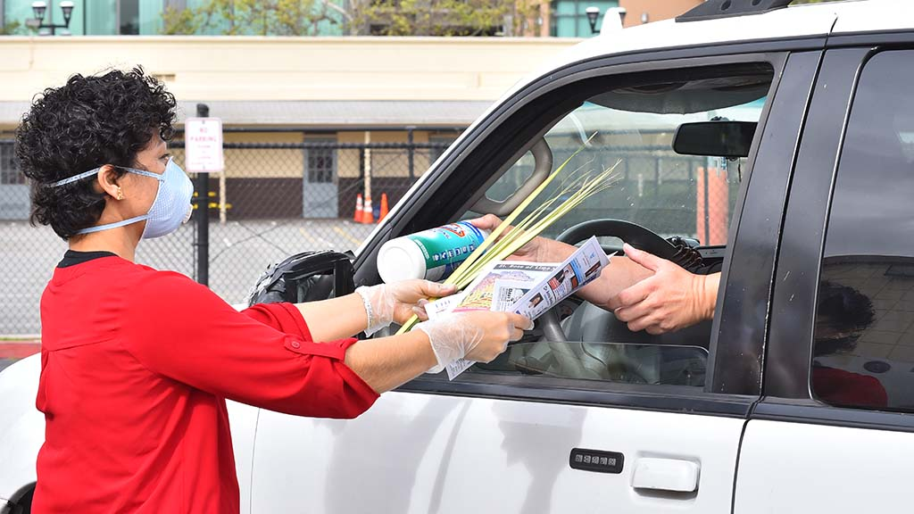 A church worker hands palms, a church bulletin and newspaper to a parishioner and gets disinfectant wipes in return.