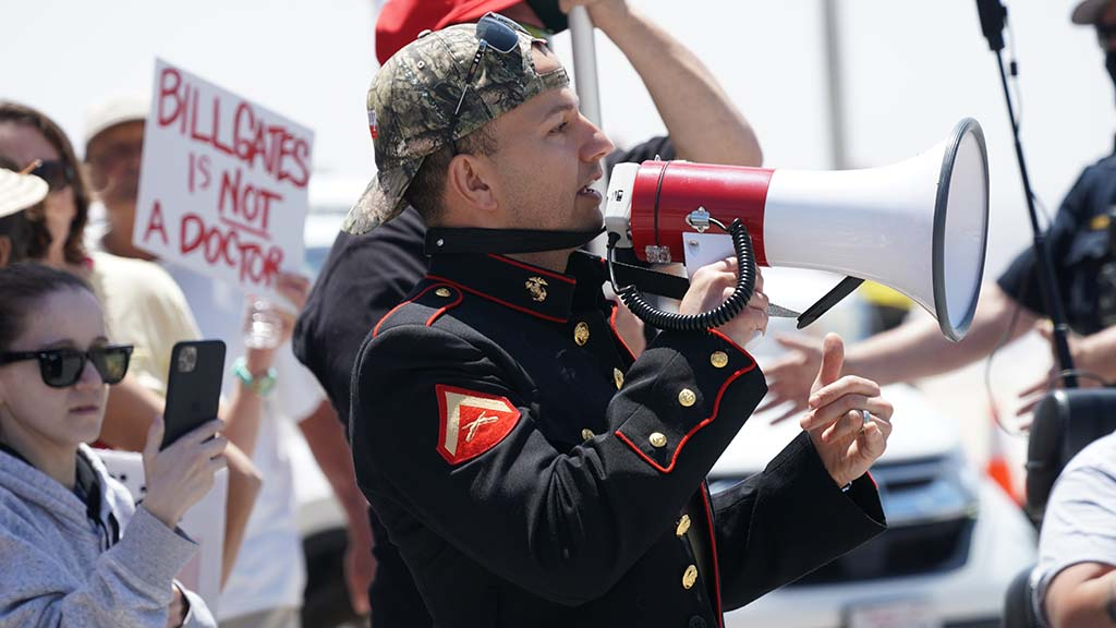A protester in a U.S. Marine jacket addresses protesters in Pacific Beach.