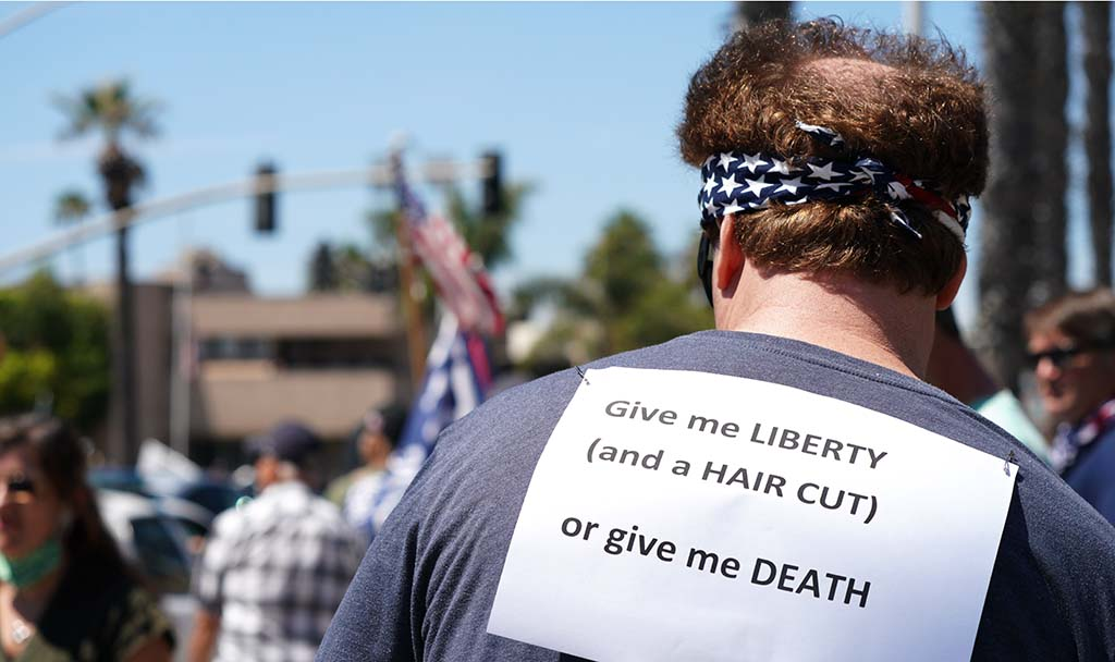 Protester shows his priorities with a sign on his back.