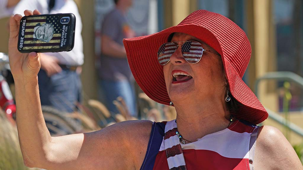 A President Trump supporter speaks into her phone as she walks down the sidewalk along Mission Boulevard in Pacific Beach.