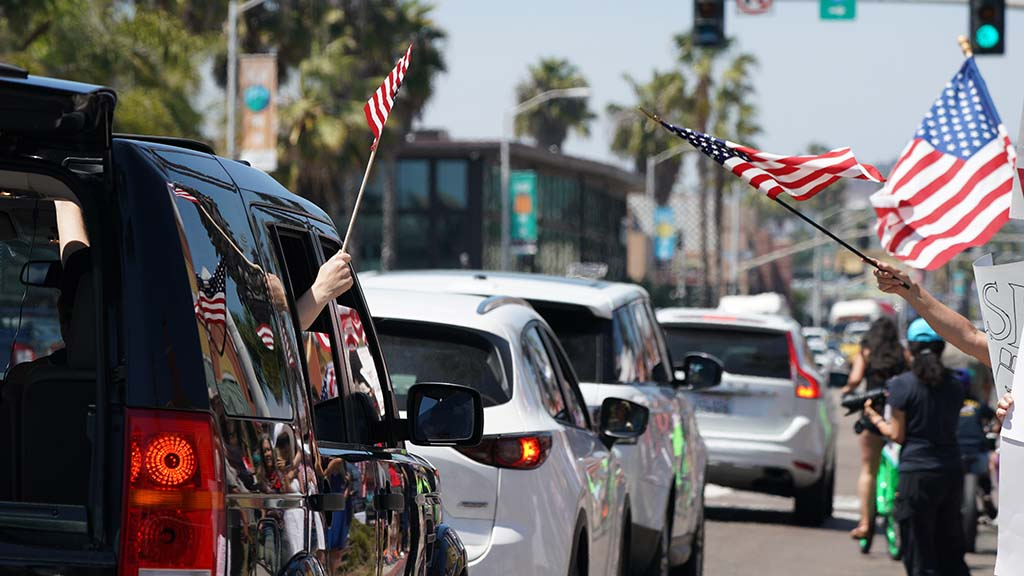 People circled Mission Boulevard, honking horns, to lend support to protesters in Pacific Beach
