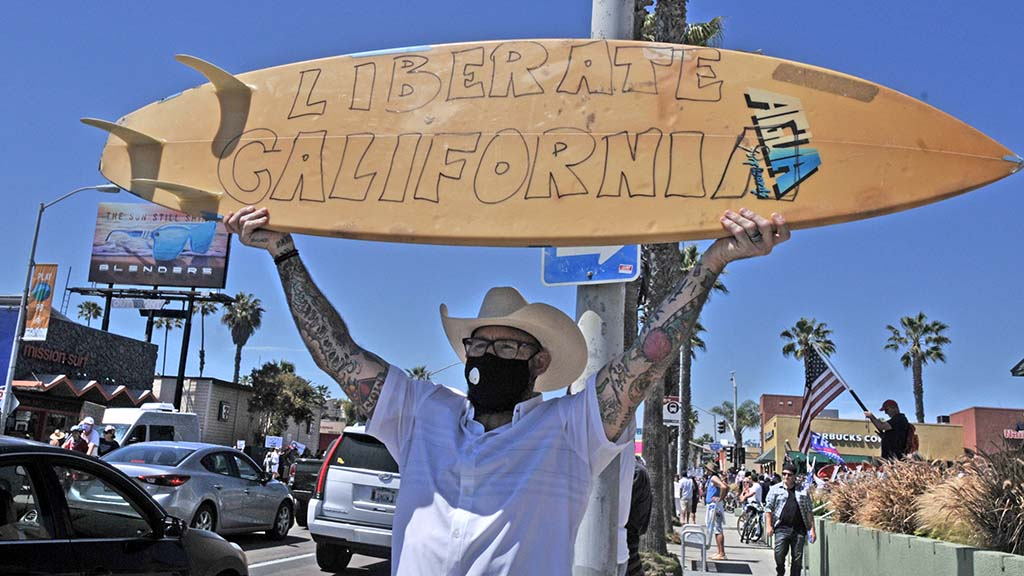 A protester using his surfboard as a sign gets drivers' attention in Pacific Beach.