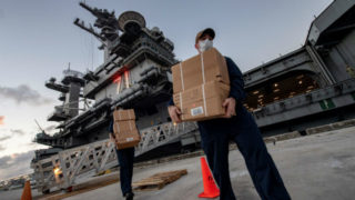 Sailors wearing face masks unload supplies from the USS Theodore Roosevelt