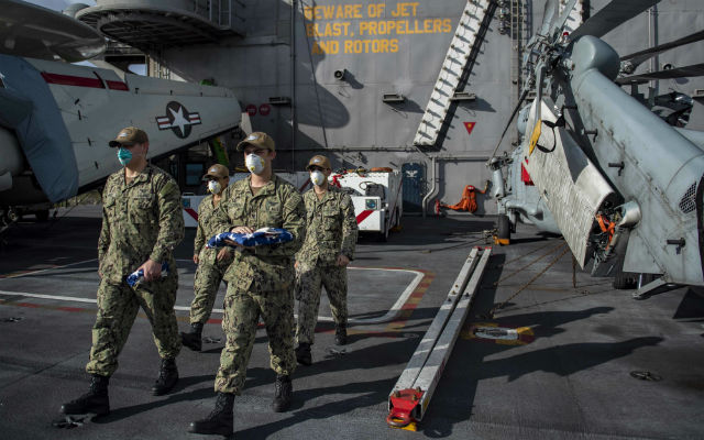 Sailors carry the flag to conduct morning colors aboard the USS Theodore Roosevelt