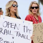 Crista Anne Curtis (left) holds sign at April 19 protest near Swami's State Beach in Encinitas.