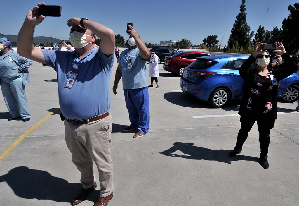 La Mesa hospital workers wave at and record planes taking part in fly-over of five San Diego County hospitals.