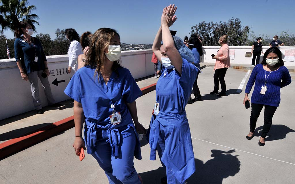 Sharp Grossmont Hospital workers in scrubs applauded fly-over by group of five planes.