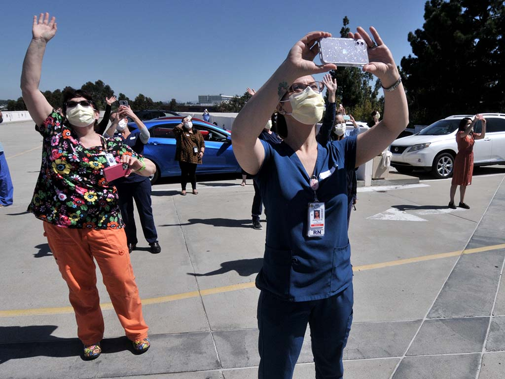 La Mesa hospital workers wave at and records planes taking part in fly-over of five San Diego County hospitals