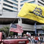 The so-called Gadsden flag was carried by protesters and mounted on vehicles passing by.