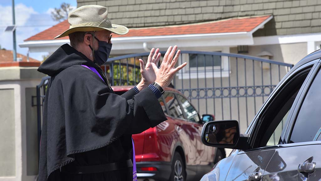The Rev. Jim Retzner of St. Patrick's Catholic Church speaks to a person at a drive-thru confessional