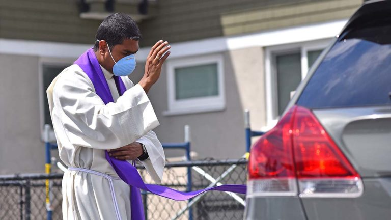 The Rev. Carlos Medina blesses a parishioner as he gives absolution at the end of a confession in his church's parking lot.