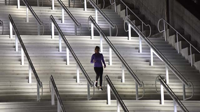 A lone jogger gets exercise running up and down stairs at the San Diego Convention Center at night.