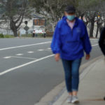 People in face masks walk in Del Mar