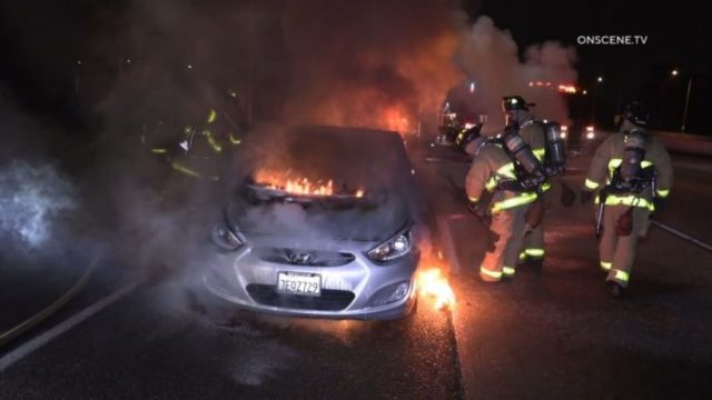 Firefighters work to douse the burning car
