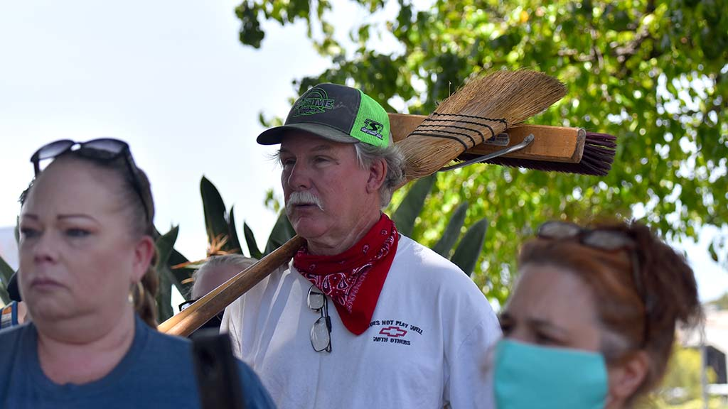 A man with brooms joins a prayer grouping in downtown La Mesa as volunteers cleaned up Sunday morning.