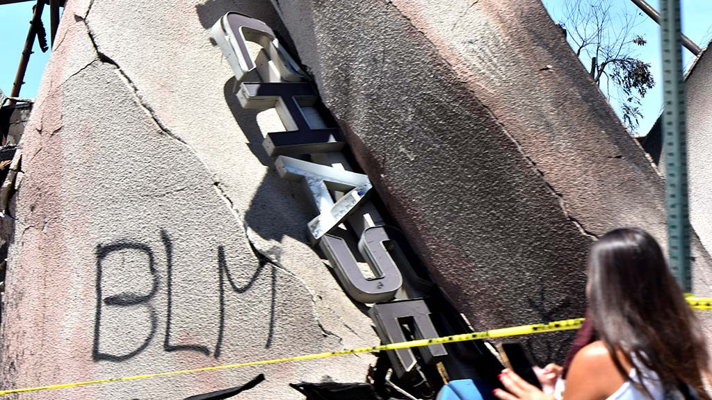 A Chase Bank sign lies in the debris of the burned building that was attacked by protesters.