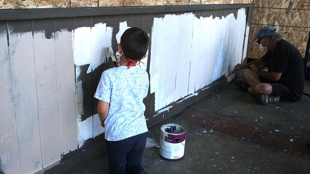 Families members showed up at the La Mesa Springs Shopping Center Sunday morning to paint, clean and board up broken windows.