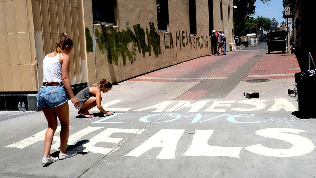"""Grossmont High School students Sofia Kruse, 15, and Meakalia Gilnan (kneeling), 16, made a chalk message saying """"La Mesa love heals"""" next to a historic building that was gutted by fire by protesters"""