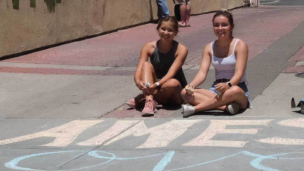 """Sofia Kruse and Meakalia Gilman made a chalk message saying """"La Mesa love heals"""" next to a historic building that was gutted by fire by protesters"""