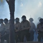 Tear gas envelops sheriff's deputies in front of La Mesa police station entrance. Photo by Chris Stone