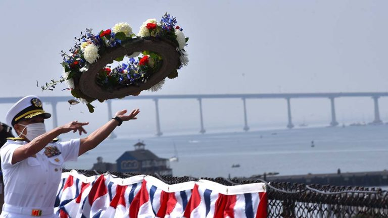 Rear Adm. Bette Bolivar, commander of Navy Region Southwest, tosses a wreath from the USS Midway into San Diego Bay.