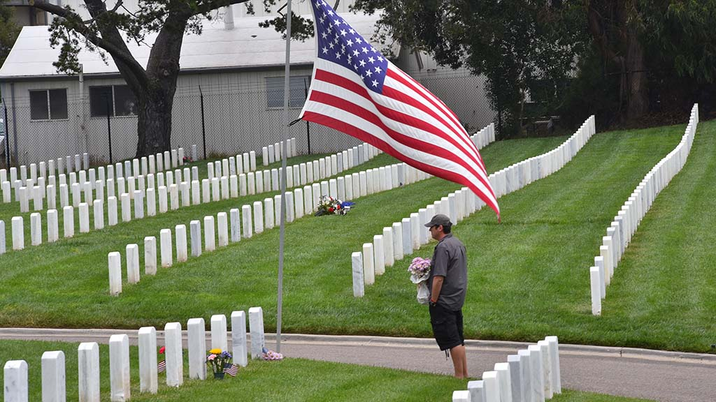 A man brings flowers to a grave at Fort Rosecrans National Cemetery. A line of cars streamed into the cemetery despite no public service.