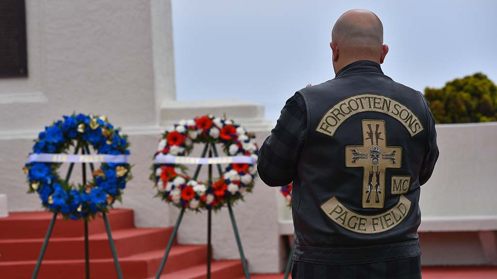 A motorcycle rider pays respect at Fort Rosecrans National Cemetery, where wreaths representing all branches of the military were presented.