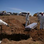 Gravediggers in protective suits bury a coronavirus disease victim