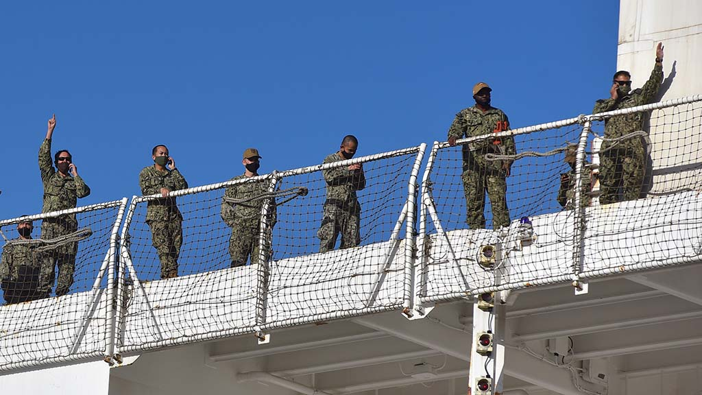 Crew members talk on cellphones and wave to people on the pier at North Island Naval Air Station.