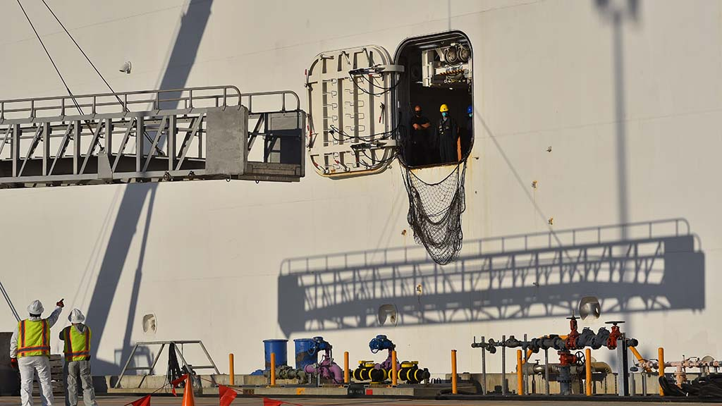 A brow is moved into position on the USNS Mercy for the crew to disembark.