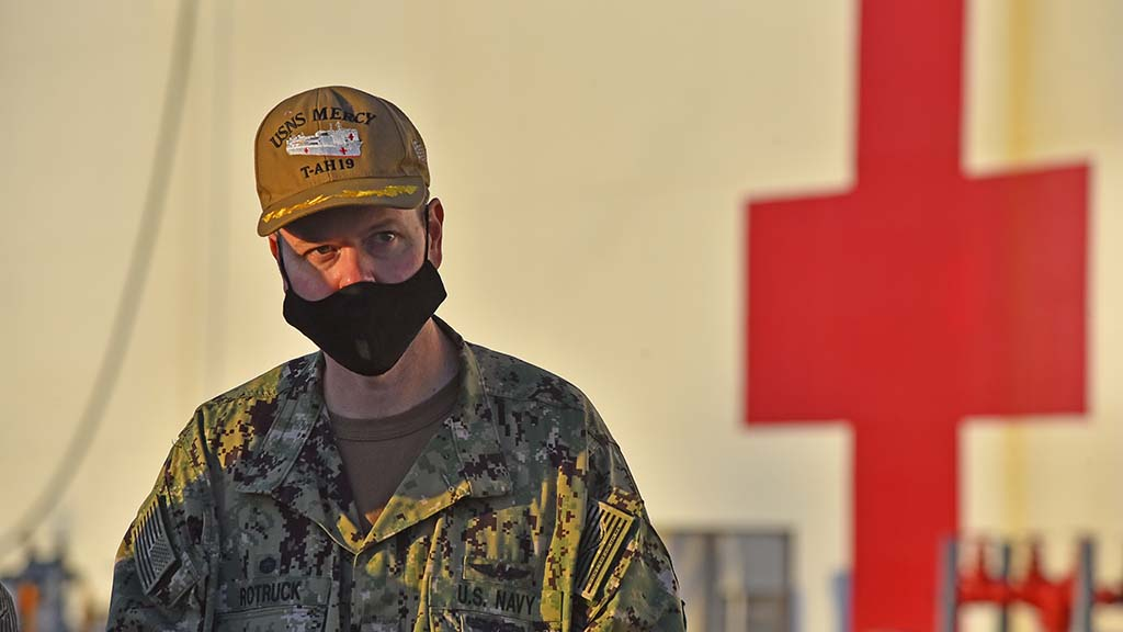 Capt. John Rotruck, commanding officer of Medical Treatment Facility of the USNS Mercy, speaks to another officer after stepping off of the hospital ship after it docked at North Island Naval Air Station Thursday evening.