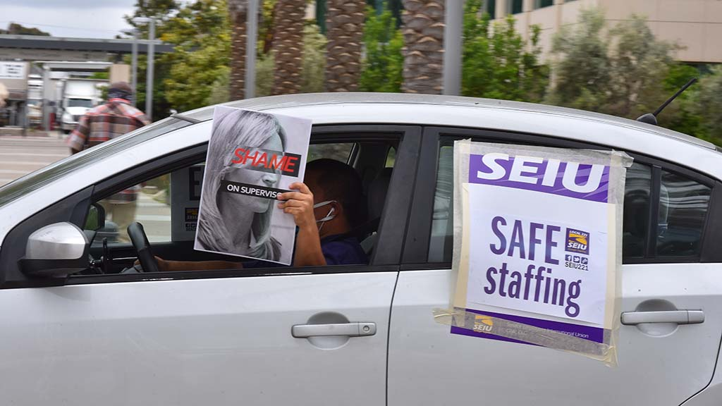"""Dubbed the """"Supervisors Caravan of Shame,"""" county union workers pressed for better protective gear and hazard pay in front of the county operations building in Kearny Mesa."""