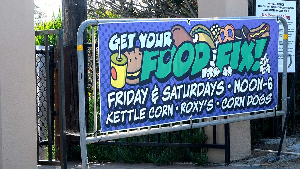 Signs at the Del Mar Fairgrounds announce fair food sales Friday and Saturday afternoons via the Solana Gate.
