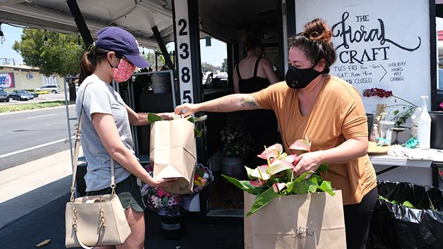 Un client de The Floral Craft sur Fletcher Parkway à El Cajon récupère des anthuriums précommandés pour la fête des mères auprès de la propriétaire du magasin Danielle Sanchez (à droite).