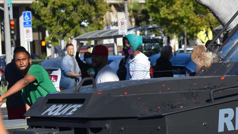 Young man in green follows through after launching rock crashing into police armored car that was backing up.