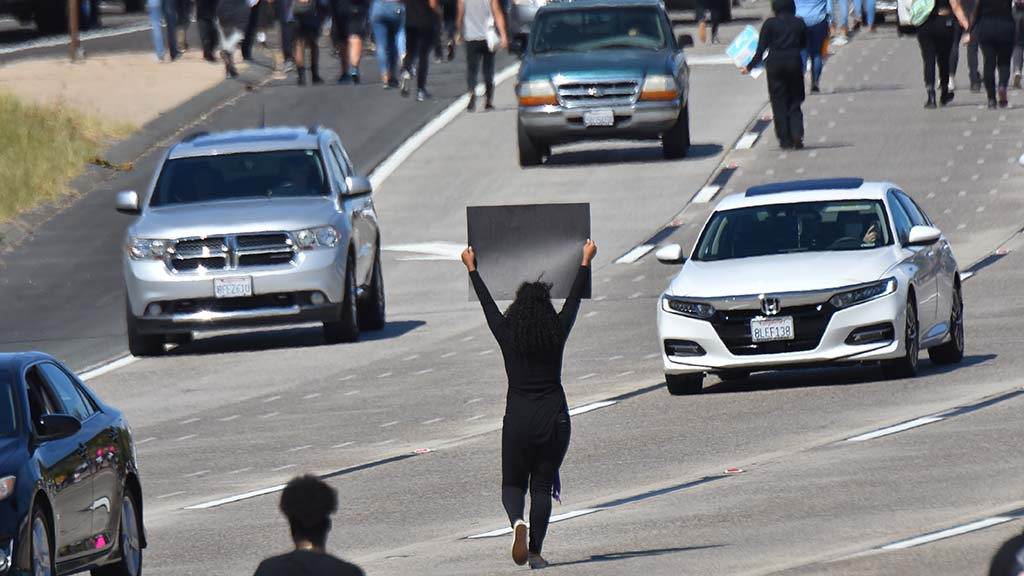 A woman holds a sign as part of an Interstate 8 blockage in La Mesa.