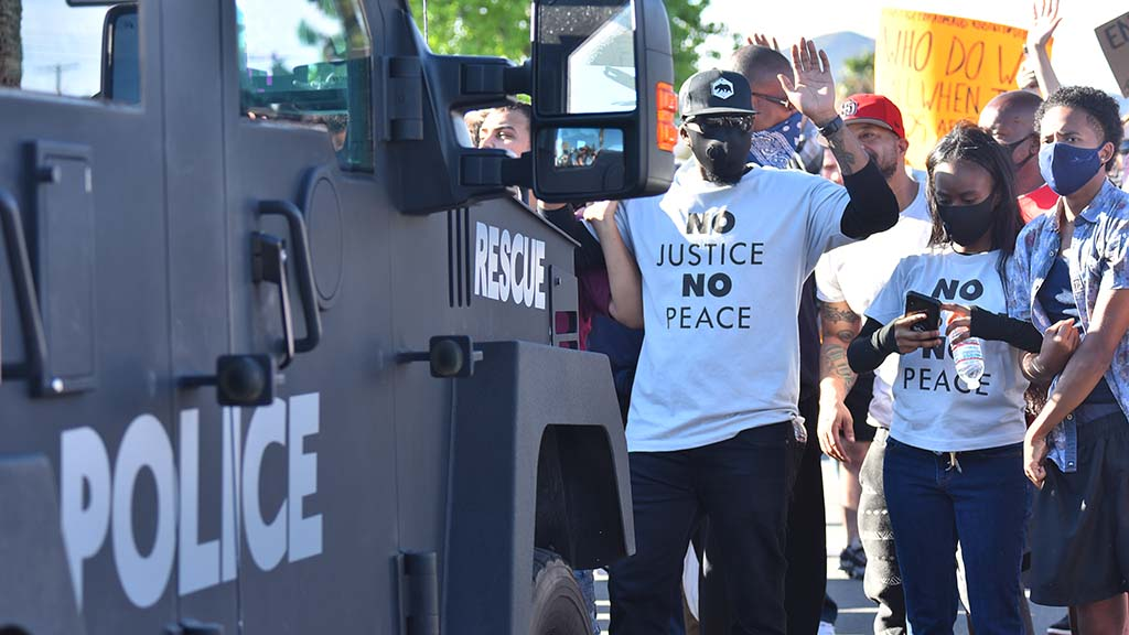 Protesters holding their hands up blocked a police armored vehicle from moving forward.
