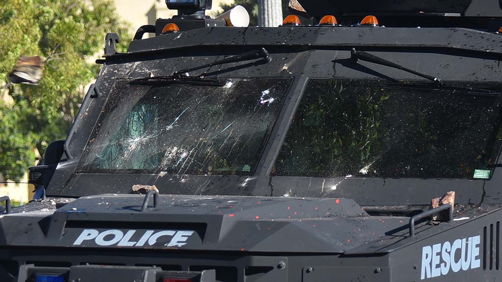 A rock (at far left) heads toward the police armored vehicle with windows already shattered in front and on passenger side.