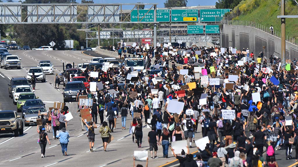 Hundreds flood Interstate 8 in la Mesa as part of a day of peaceful protest and rare spasms of violence.