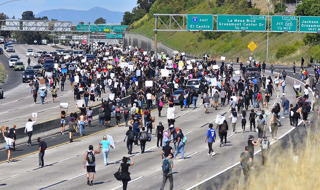 Protesters led to east and westbound Interstate 8 in La Mesa being shut down by authorities. Photo by Chris Stone
