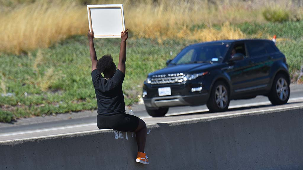 A woman sits on Interstate 8 median as part of La Mesa protests.