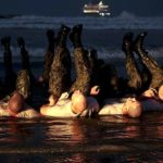 SEAL candidates perform physical training on the beach during Basic Underwater Demolition/SEAL (BUD/S) training at Naval Special Warfare Center in Coronado.